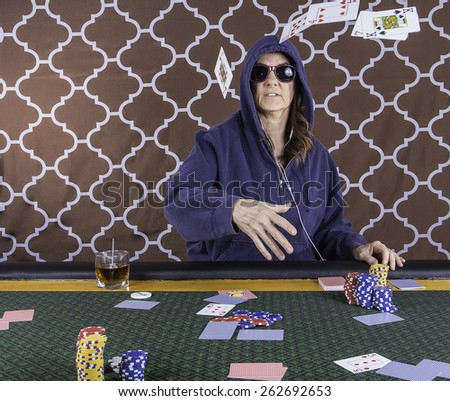 A woman sitting at a poker table wearing sunglasses and hoodie throwing the playing cards - stock photo