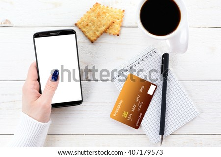 A woman sitting at a white wooden table and pay for purchases via smartphone - stock photo