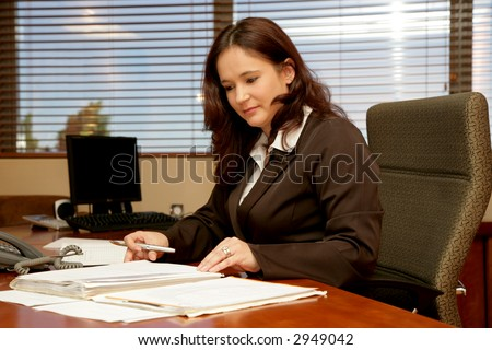 A woman sitting at her desk in a office - stock photo
