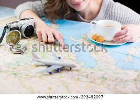 A woman sitting at table with a map with a paper airplane, compass and camera and visualises his desire to travel. Shallow depth of field - stock photo