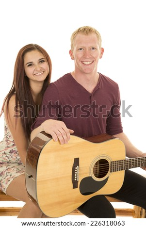 a woman sitting behind her man, who is holding on to a guitar. - stock photo