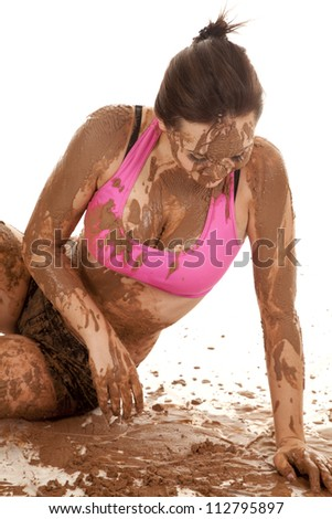 A woman sitting in a bunch of mud, with mud all over her body. - stock photo