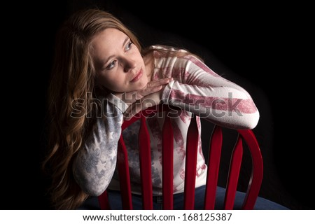 A woman sitting in a chair looking to the side, her face is shadowed. - stock photo