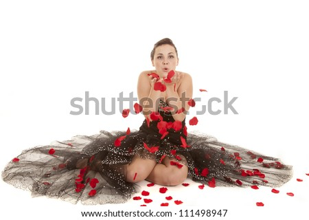 a woman sitting in her black dress with rose petals all around her blowing them off of her hands. - stock photo