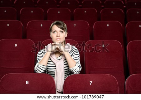 A woman sitting in the movie theatre - stock photo