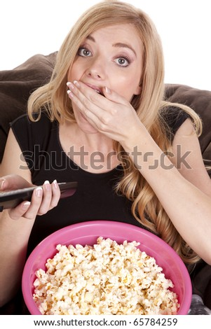 a woman sitting on a bean bag while she is enjoying her popcorn while she is watching tv - stock photo