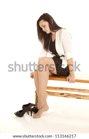 A woman sitting on a bench resting her feet by taking off her shoes. - stock photo