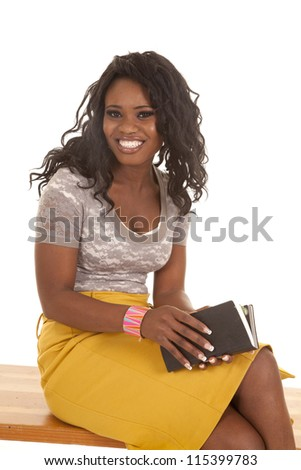 a woman sitting on a bench with a smile on her face holding on to her book - stock photo
