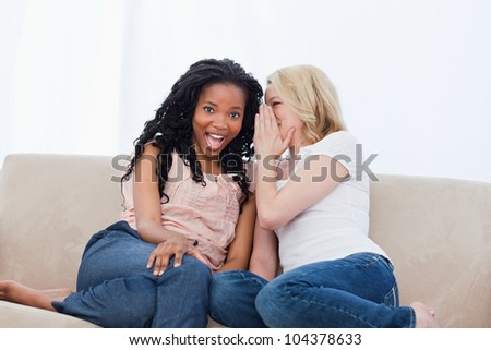 A woman sitting on a couch is whispering into her surprised friends ear - stock photo