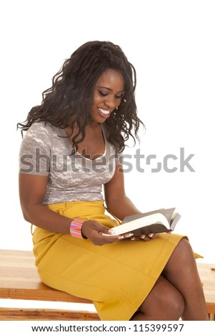 a woman sitting on a wooden bench reading a book. - stock photo