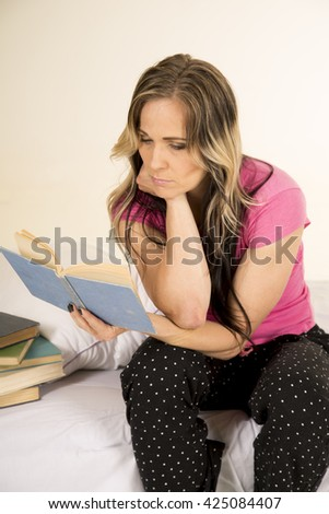 a woman sitting on her bed reading a book with a serious expression. - stock photo
