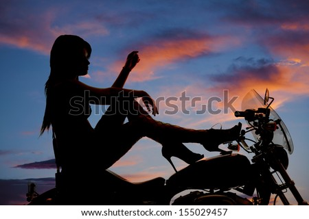 A woman sitting on her motorcycle with her heels on the tank of the bike - stock photo