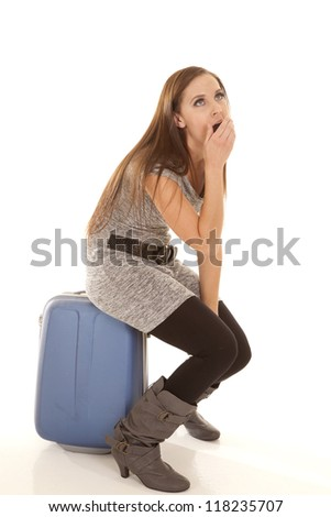 a woman sitting on her suitcase bored with what is going on. - stock photo