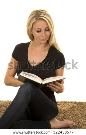 a woman sitting on the carpet reading a book looking down. - stock photo