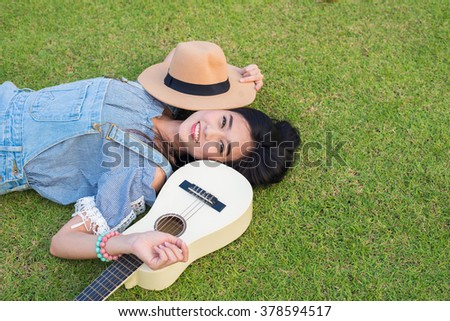 a woman smile with her guitar with her head down, sitting on playground - stock photo