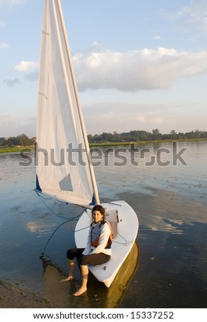 A woman smiling as she sits on the edge of the sailboat.  She is smiling, dangling her feet in the water, and looking away from the camera.  Vertically framed shot. - stock photo