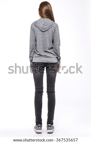 A woman stand up wearing black denim(pants, trousers, jean) and black leather boots and grey hood shirts for fall, outdoor, sports back side isolated white at the studio.  - stock photo