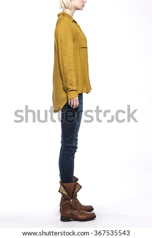 A woman stand up wearing blue denim(pants, trousers, jean) and black leather boots and indian yellow t-shirts(top) for fall back side view isolated white at the studio.  - stock photo