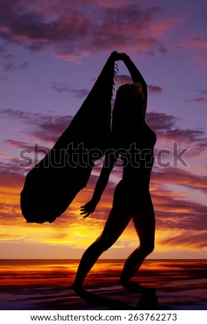 a woman standing and letting her sarong blow in the wind. - stock photo