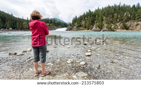 A woman standing by a river watching a waterfall in the Canadian Rocky Mountains. - stock photo