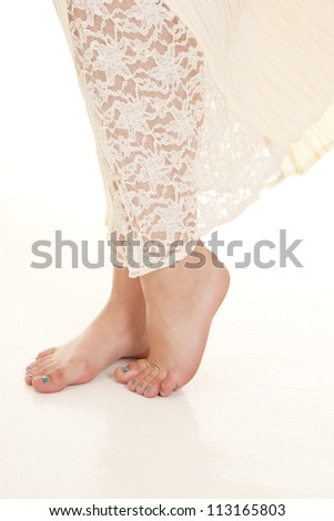 A woman standing in her lace dress with her bare feet showing. - stock photo