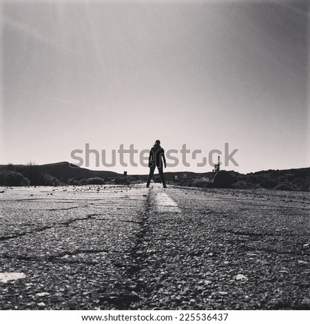 A woman standing in the middle of a two lane road. - stock photo