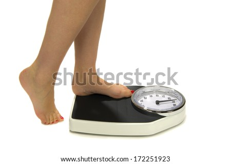 A woman standing on a weight scale  - stock photo