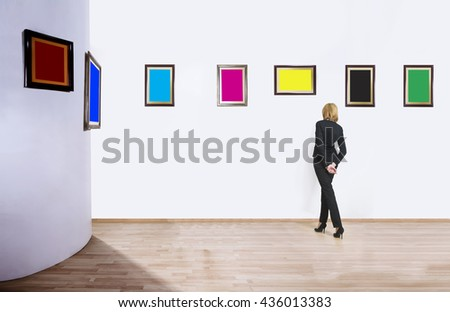 A woman standing with her back and looking at blank of one color frames in art gallery. - stock photo