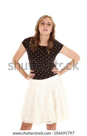 A woman standing with her hands on her hips with a serious expression on her face. - stock photo
