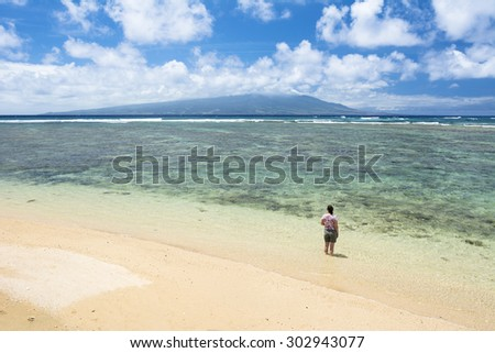 A Woman stands in warm, tropical water on a beach in Molokai Hawaii.  - stock photo