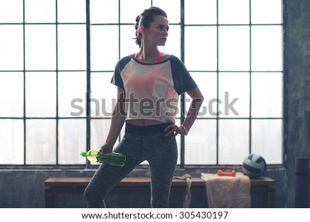 A woman stands relaxing, looking off to the side, holding a water bottle in a loft gym after a good workout. - stock photo