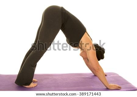 A woman stretching out her body doing a yoga stretch. - stock photo
