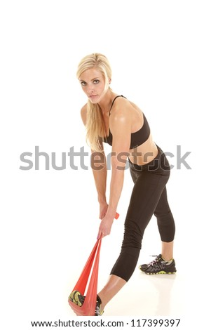 a woman stretching out her calf with a band. - stock photo