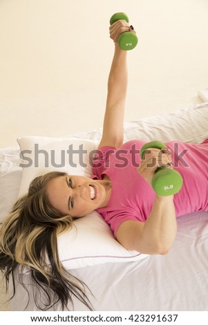 A woman struggling to lift her weights and get out of bed. - stock photo