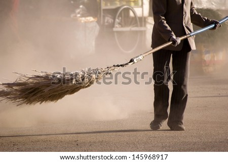 A woman sweeping a street (Xiahe, China) - stock photo