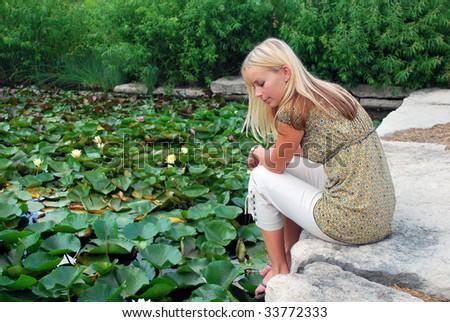 A woman thinking near a pond - stock photo