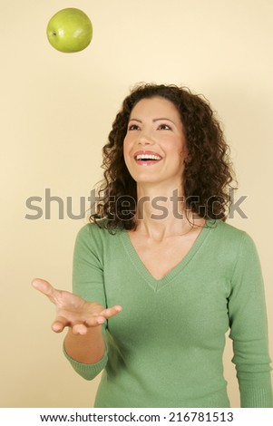 A woman throwing an apple in the air. - stock photo