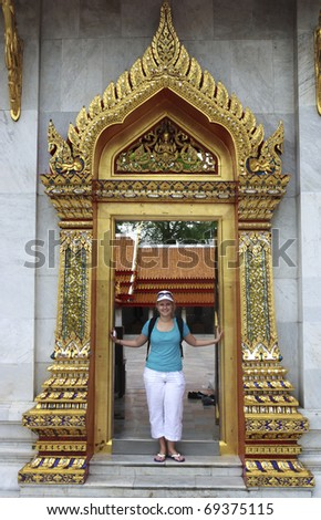 A woman tourist in a doorway of a temple in Bangkok - stock photo