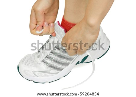 A woman tying a sport shoe; clipping path - stock photo