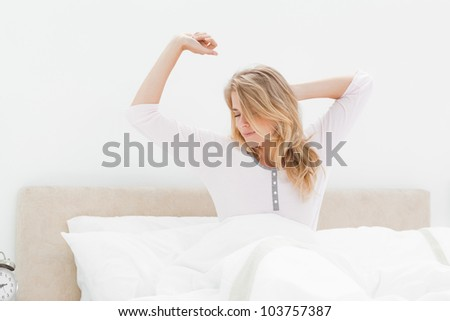 A woman upright in bed, one arm stretching  and the other behind her head which is turned to the side. - stock photo