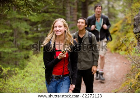 A woman using a GPS in the forest on a camping hike - stock photo