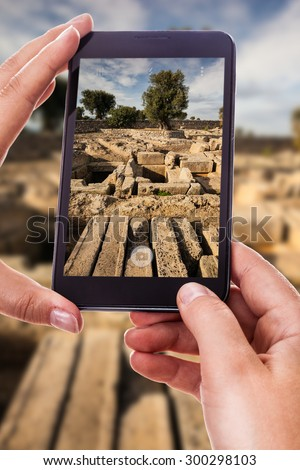 a woman using a smart phone to take a photo of a view of the ruins of Gnatia, Italy - stock photo