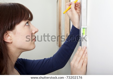A woman using a spirit level to complete a DIY task. - stock photo