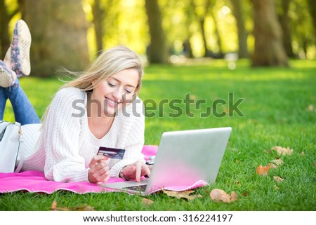 A woman using credit card shopping online with a laptop in the park - stock photo