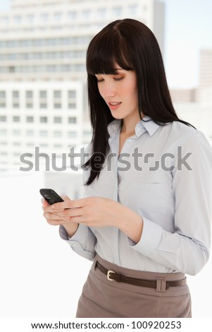 A woman using her phone to send a text message at work - stock photo