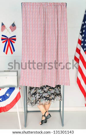 A woman voter inside a Voting Booth at his local polling place. - stock photo