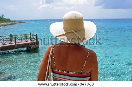 A woman waits alone on the shore of a Caribbean island - stock photo