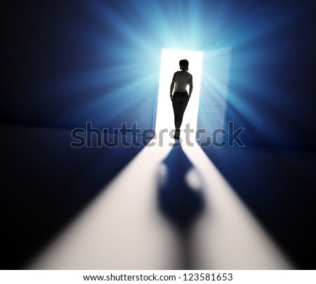 A woman walking into the light through open door - stock photo