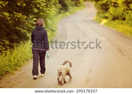 A woman walking the dog on a silent road. Image has a vintage effect. Dog breed is Lagotto romagnolo also known as Italian waterdog. - stock photo