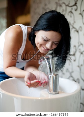 A woman washing her hands in the sink - stock photo